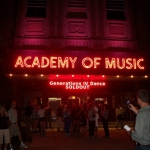 Front view of the Academy of Music in Northampton, MA with neon bright red sign